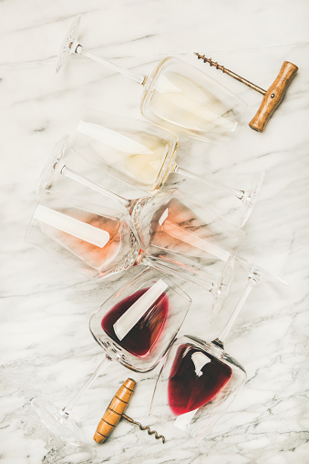 istock Red, rose and white wine in glasses and corkscrews 1058793898