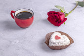 red rose, heart-shaped cake and coffee Cup on concrete background
