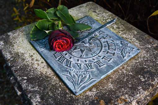 Red rose lying on a weathered sundial