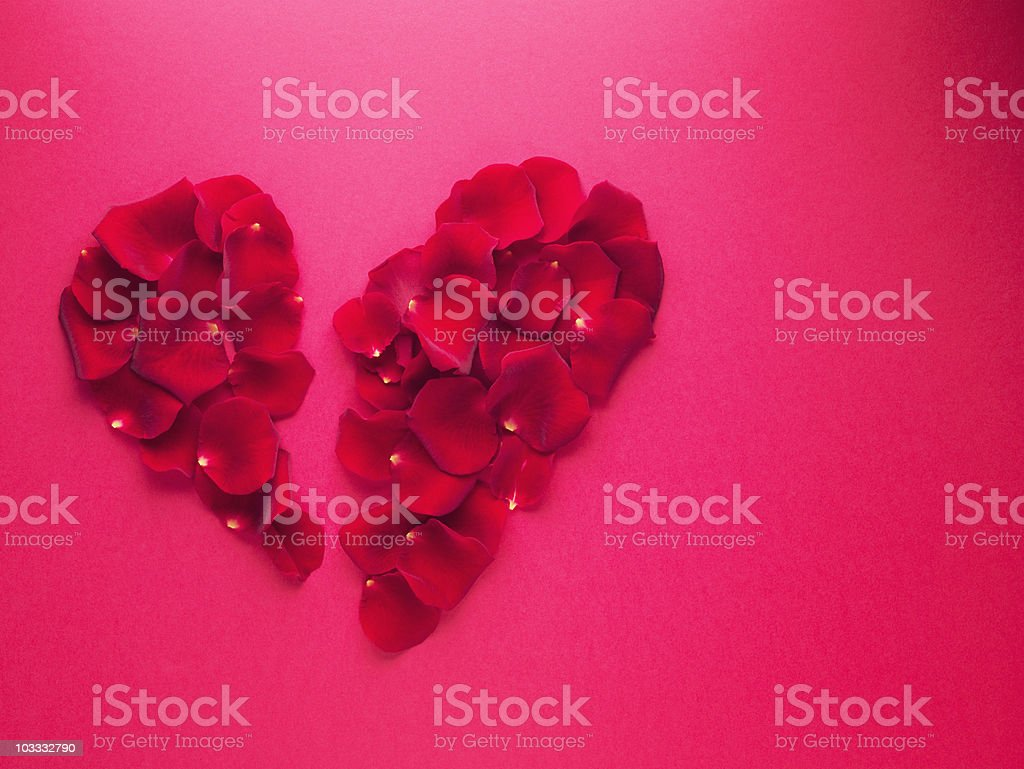 Red rose petals forming broken heart-shape royalty-free stock photo