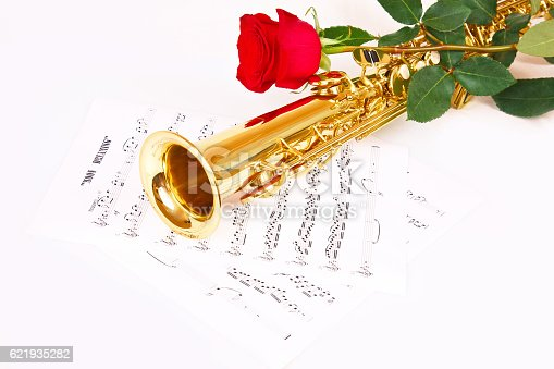 Red rose, saxophone and music sheet on a white background