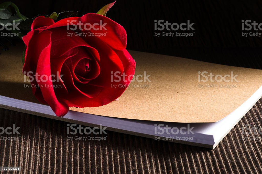 Red rose top of book and brown fabric