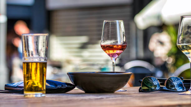 A red - rose wine glass placed on a wooden table next a bowl and other glasses, outdoors stock photo