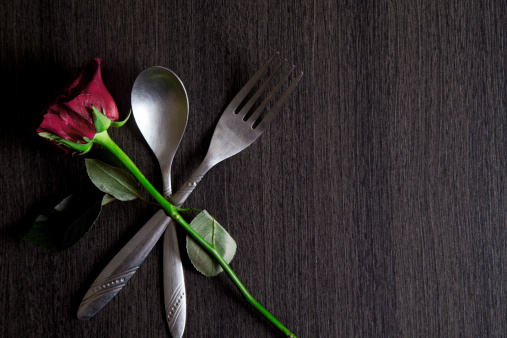 Red rose with spoon and fork on brown wooden table