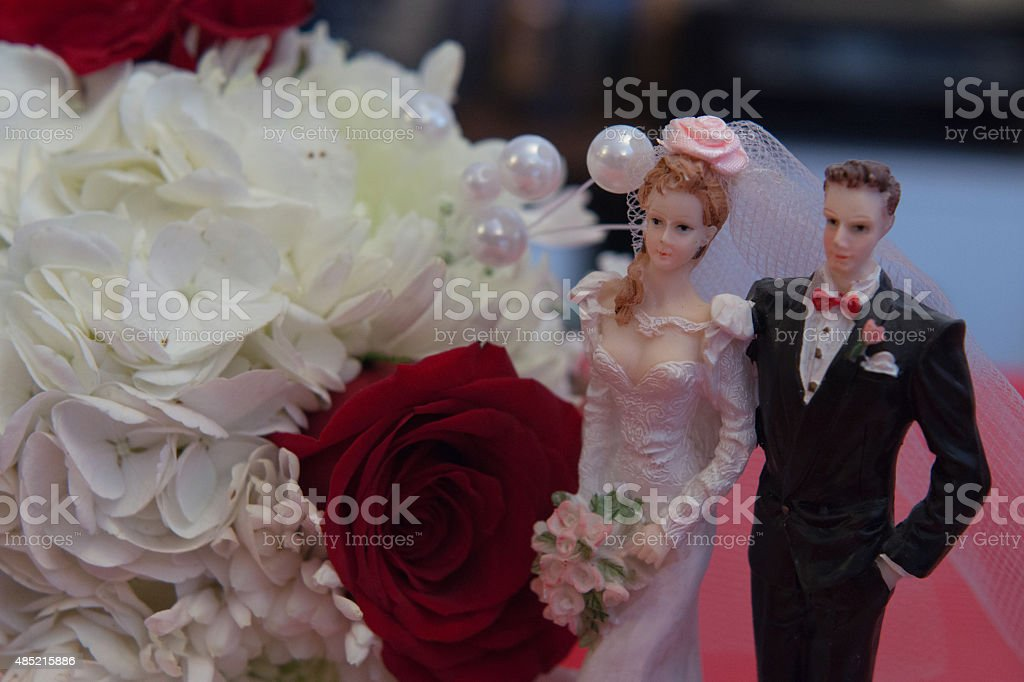 red rose with white flowers with bride and groom figurine stock photo