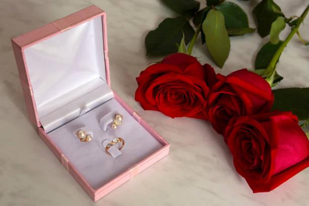 rote rosen und eine schachtel mit goldschmuck auf marmor hintergrund. valentinstag, hochzeit oder geburtstag-konzept - ohrringe rose stock-fotos und bilder