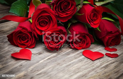 Red roses  with  hearts on a old wooden table
