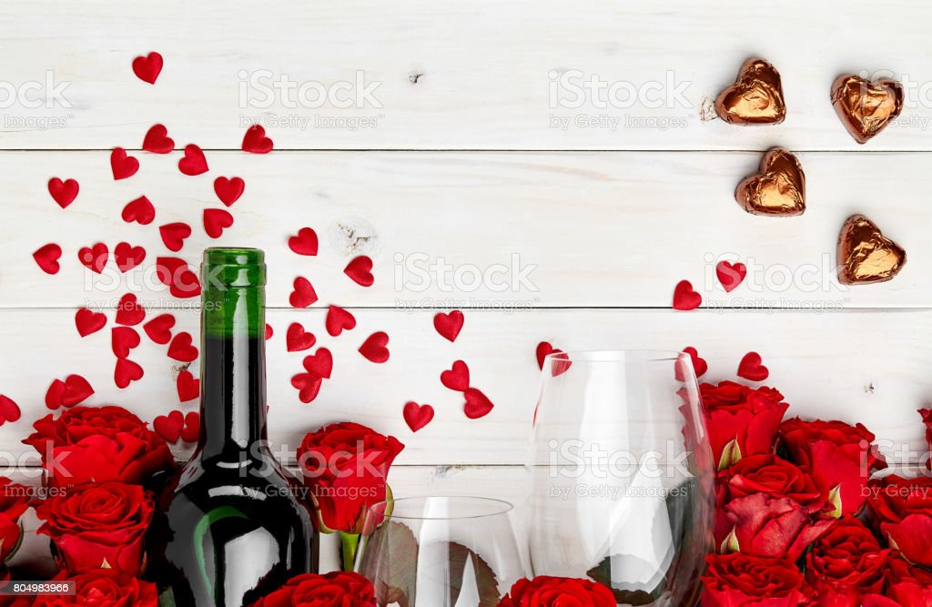 Red roses and wine on table