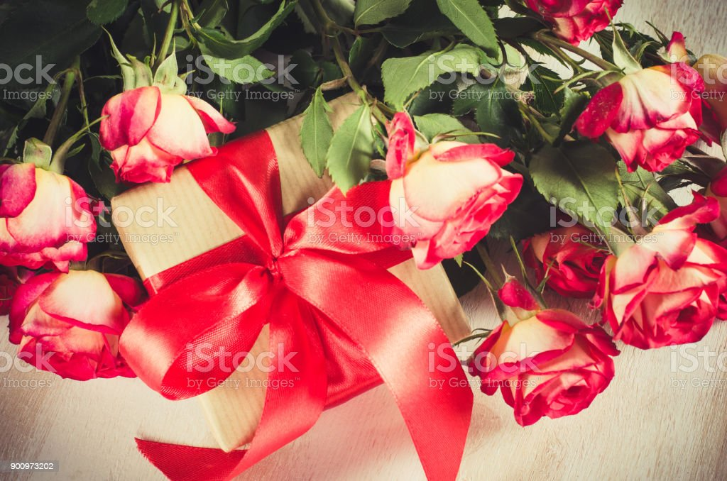 Red roses bouquet and present on wooden table. stock photo