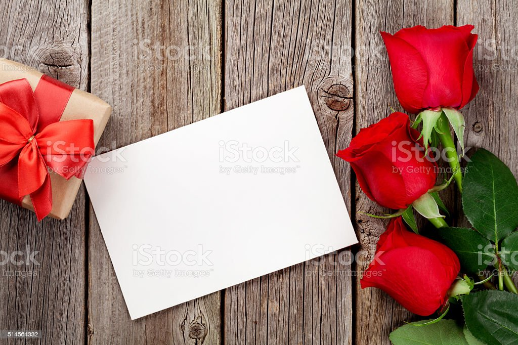 Red roses, greeting card and gift box over wooden background. Top...