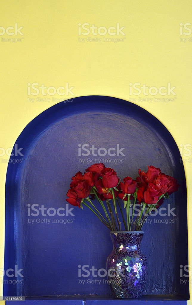 Red roses in a nook in the wall stock photo