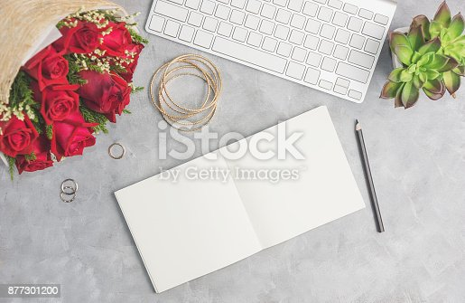 Red roses on grey table with white keyboard, open notebook and boho jewelry. Artist workplace, office concepr. Text space