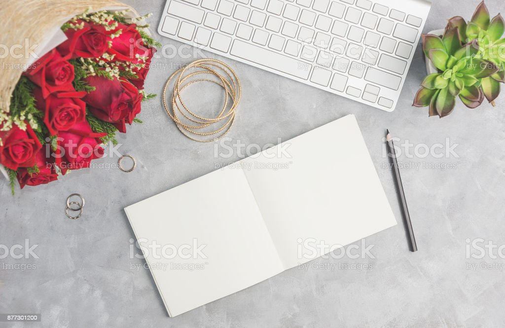 Red roses on grey table with white keyboard, open notebook and boho jewelry stock photo