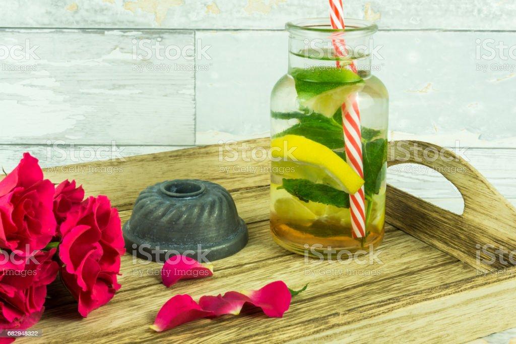 Red roses with a bio lemonade on a wooden table foto de stock libre de derechos