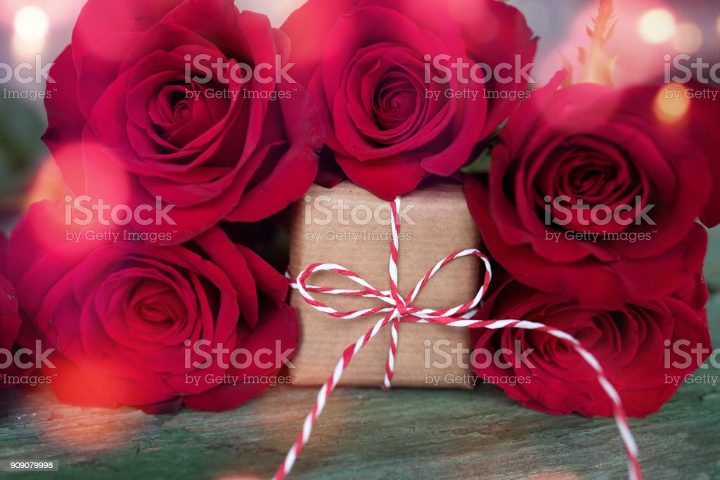 Red roses with a gift for valentines day stock photo