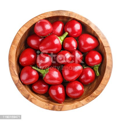istock Red round chili peppers, hot hilli pepper large cherry  in wooden bowl isolated on white. Top view 1190159471