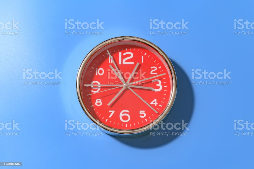 Red round clock with a large number of hands with large white numbers...