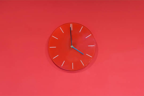 Red round modern analog glass clocks hang on a red wall. Shows the current time 4:00 pm stock photo