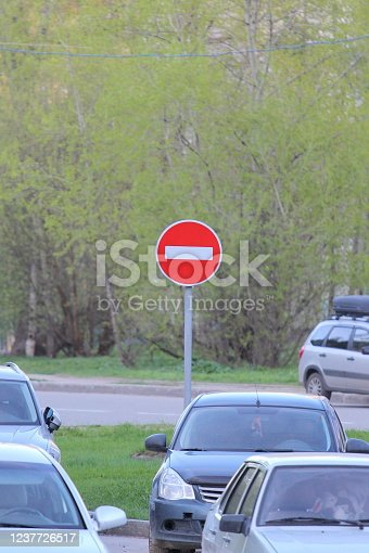 istock Red round road sign with white stripe prohibiting movement on a city street with cars. Do not enter. concept of prohibition, dead end, hopelessness and stop 1237726517