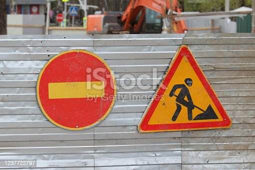 istock Red round road sign with yellow stripe prohibiting movement and Sign road works, road repair on the fence of sheet iron. Do not enter. concept of prohibition, dead end, hopelessness and stop 1237722797