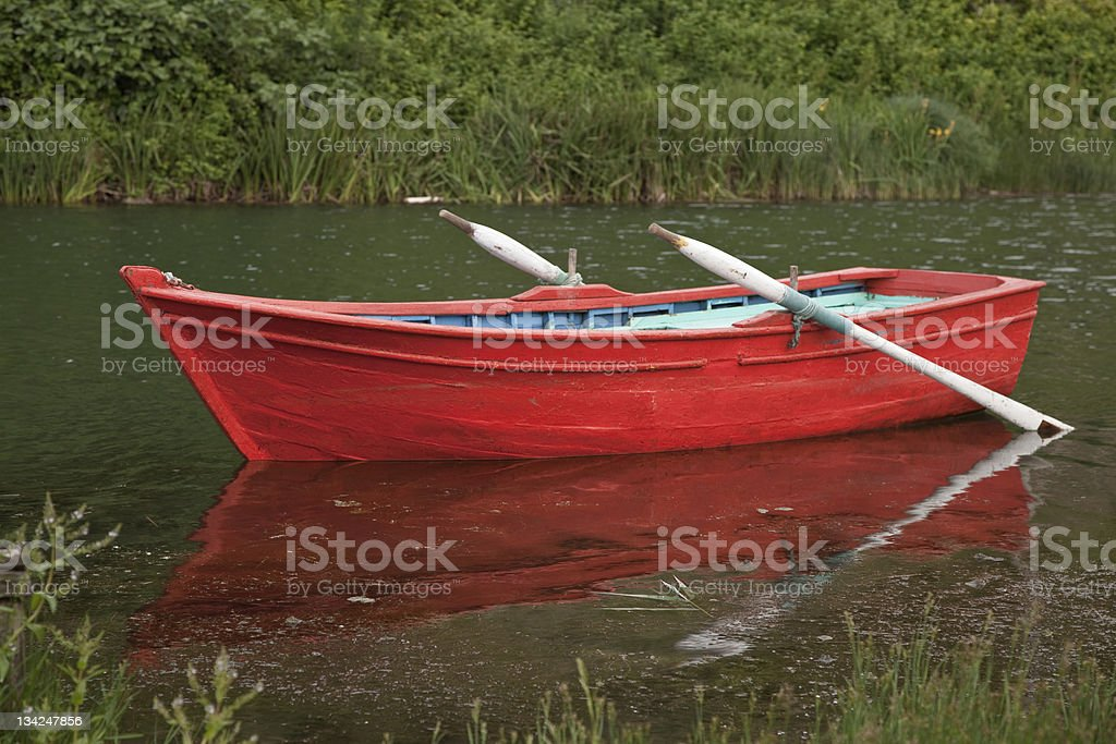 Red row boat with white oars sits in a murky watered bayou stock photo