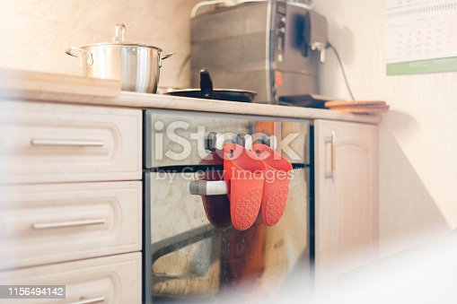 839034546 istock photo Red rubber kitchen mittens. Hang on an induction cooker. It also has a pan and a frying pan. Coffee machine on the background, on the kitchen. Soft focus. 1156494142