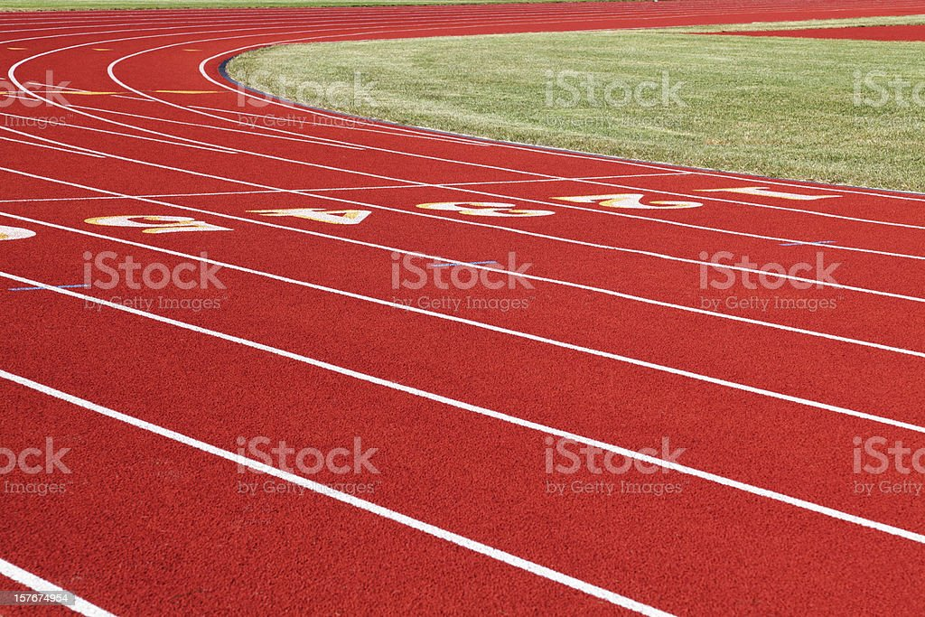 Red Running Track Numbered Lanes with White Lines royalty-free stock photo