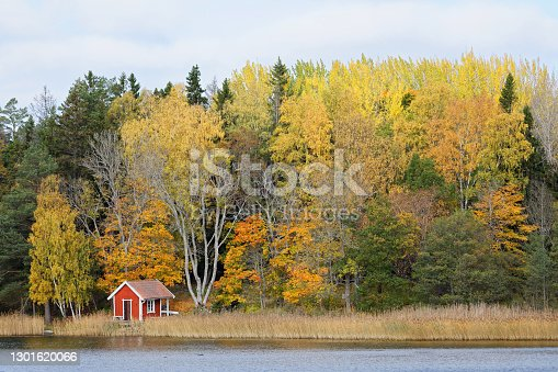 Red rural boat house and beautiful trees in warm colors during autumn