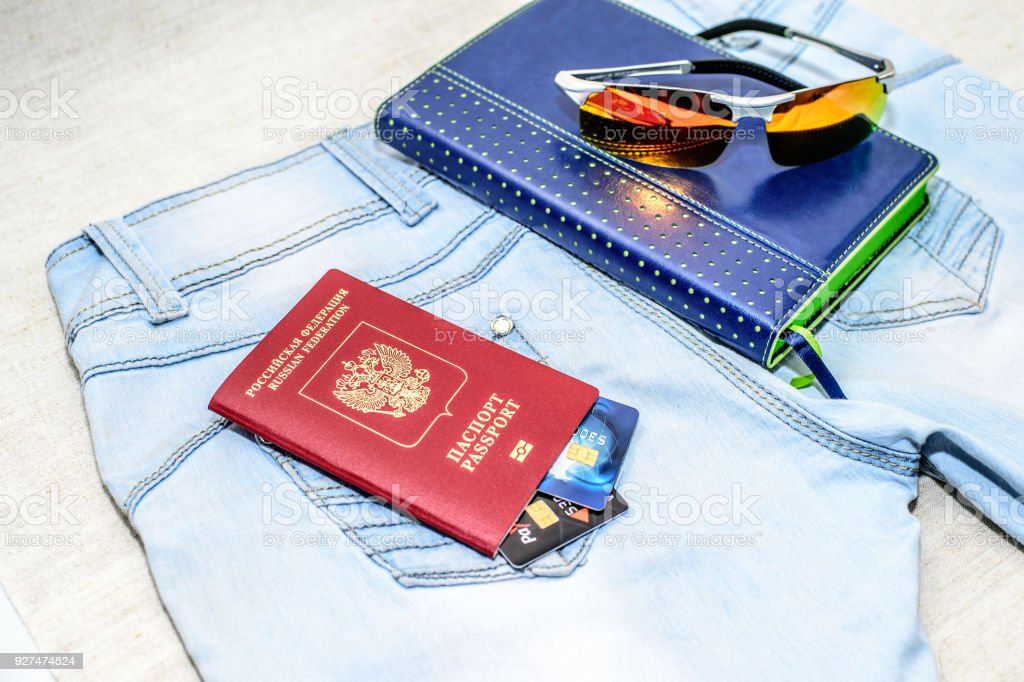 Red russian Passport with bank cards, glasses and notepad lie on jeans. The concept of travel. stock photo