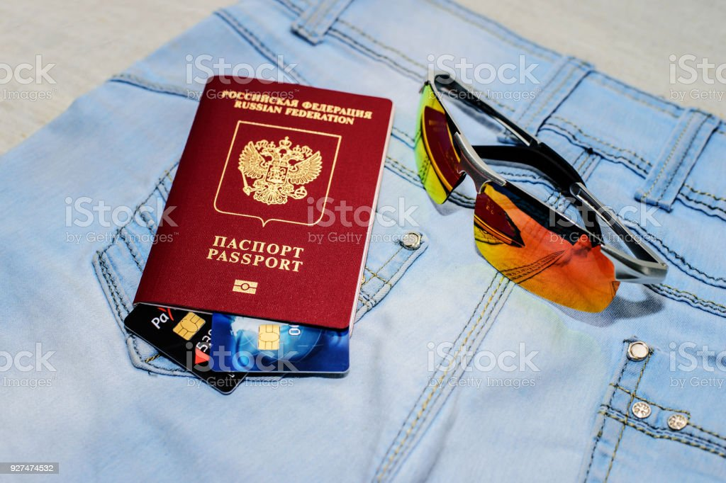 Red russian Passport with bank cards, glasses and seashells. The concept of travel. stock photo