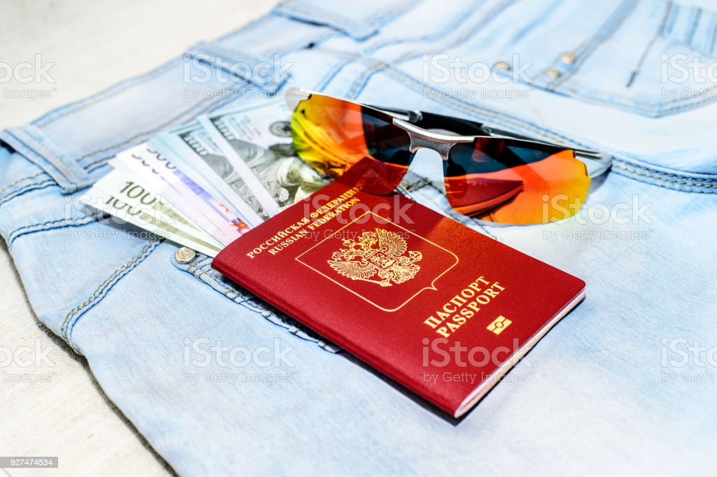 Red russian Passport with money bills, and glasses on jeans. The concept of travel. stock photo