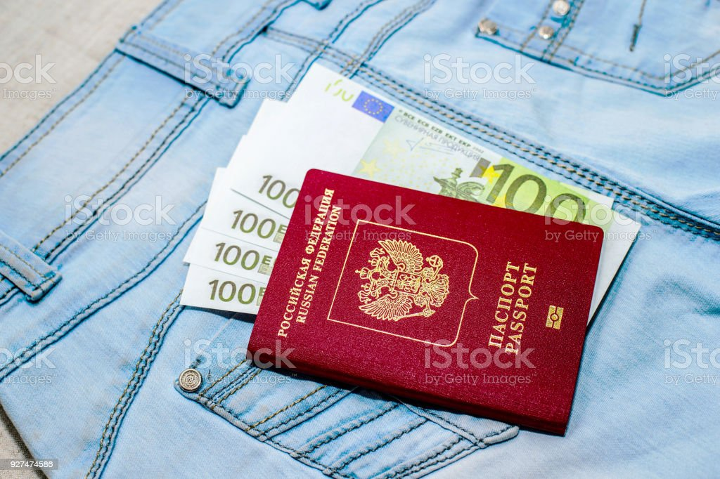 Red russian Passport with money bills on jeans. The concept of travel. stock photo