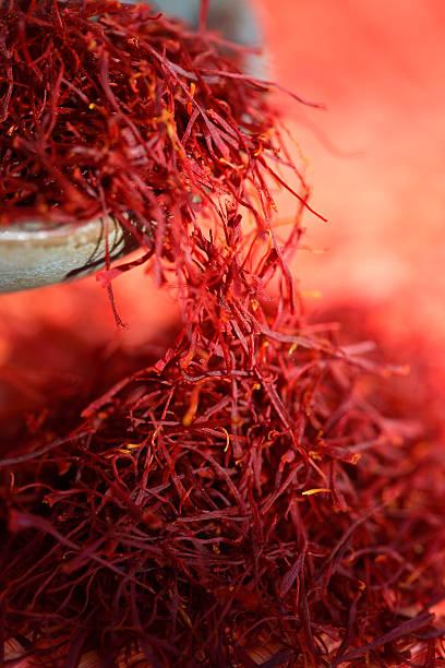 Red saffron 2. Estigmas of Crocus sativus falling from an earthen bowl. saffron stock pictures, royalty-free photos & images