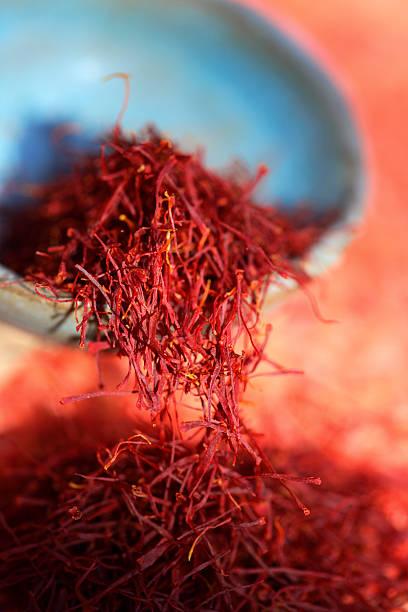 Red saffron. Estigmas of Crocus sativus in an earthen bowl and upon a table. saffron stock pictures, royalty-free photos & images