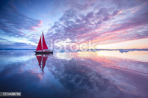 Sail boat with red sails cruising among ice bergs during midnight sun season. Disko Bay, Greenland.
