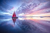 Sail boat with red sails cruising among ice bergs during midnight sun season. Disko Bay, Greenland.