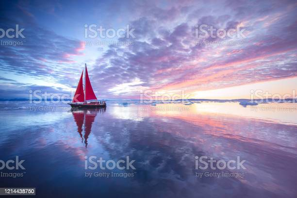 Photo of Red sail boat cruising among ice bergs in Greenland.