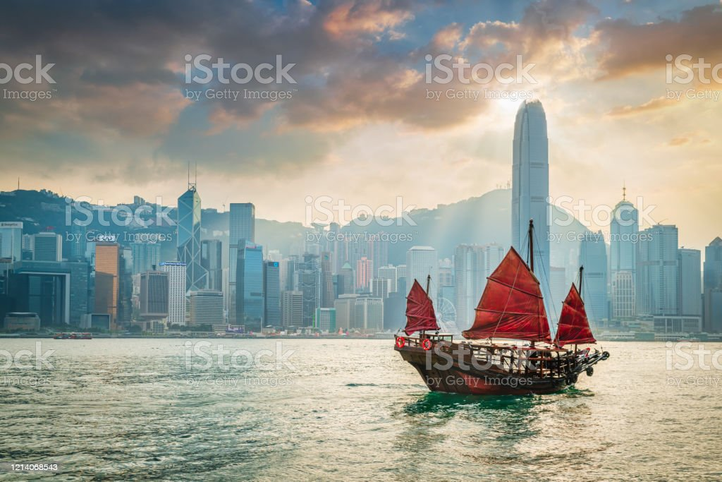 Red Sail Junkboat Cruising Along Hong Kong Cityscape at Sunset Traditional chinese junkboat with typical red sails sailing across victoria harbour under colurful amazing sunset twilight and cloudscape. Hong Kong Skyline in the Background, Hong Kong, Southeast Asia. Asia Stock Photo