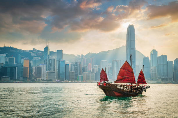 Red Sail Junkboat Cruising Along Hong Kong Cityscape at Sunset stock photo
