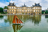 Paris, France- May 25, 2014: A Remote control sailboat complete with captain and cres navagates the calm waters of the fountain pool at the  Luxembourg Garden as visitors on the far side look on.