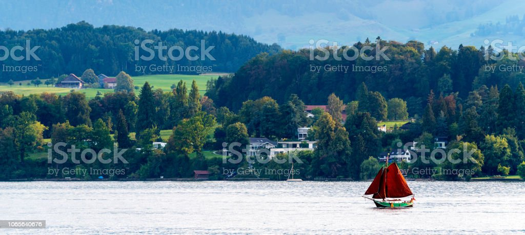 Red Sailboat On The Shore At Sunset In Lake Luzerne