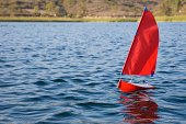 remote controlled toy sailboat sailing on lake