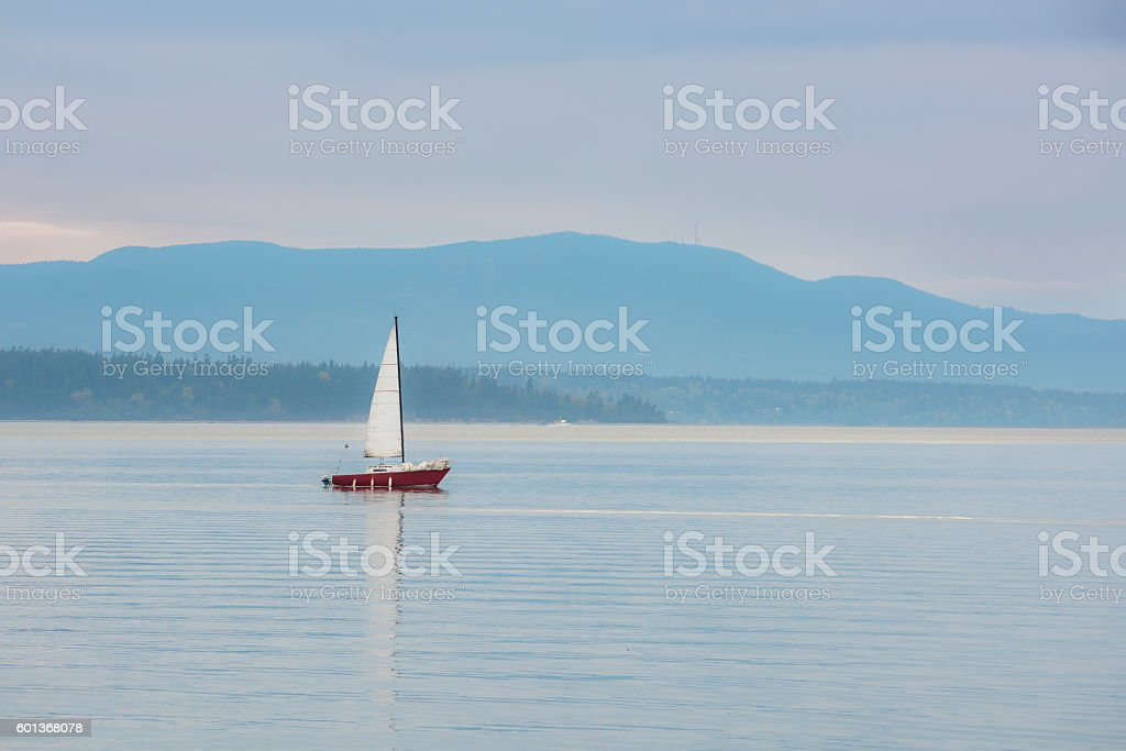 Red sailboat sailing in calm blue bay stock photo