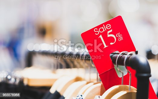 istock Red sale sign 15% discount on clothing rack in modern shopping mall or department store with copy space. Retail shop promotional event, new product discount, or business marketing advertising concept 955578988