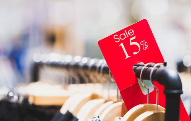 rot verkauf melden sie 15 % rabatt auf kleiderständer in modernen shopping-mall oder kaufhaus mit textfreiraum. retail-shop-promotion-veranstaltung, neue produkt rabatt oder geschäftskonzept marketing werbung - papierrollenhalter stock-fotos und bilder
