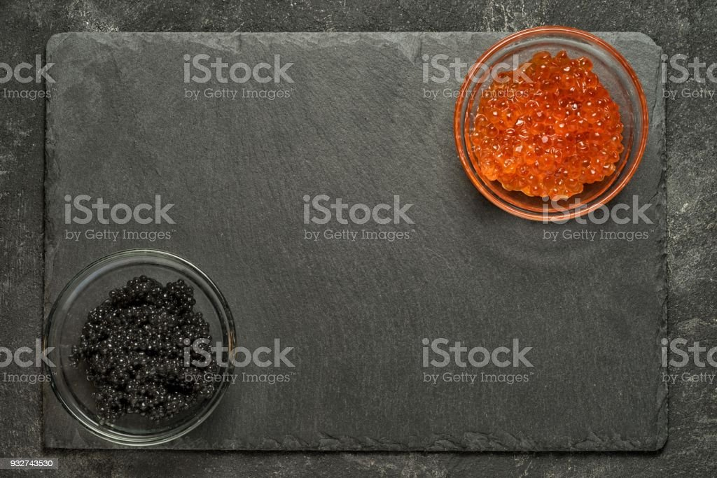 red salmon and black stugeon caviar in the opposit corners of black stone board on a black table, top view with copy space. stock photo