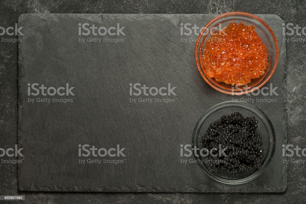 red salmon and black stugeon caviar in the side of black stone board on a black table, top view with copy space. stock photo
