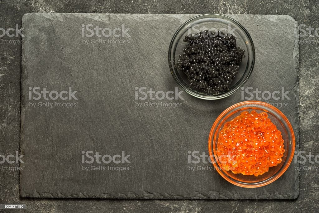 red salmon roe and black stugeon caviar on the black stone board on a black table, top view with copy space. stock photo