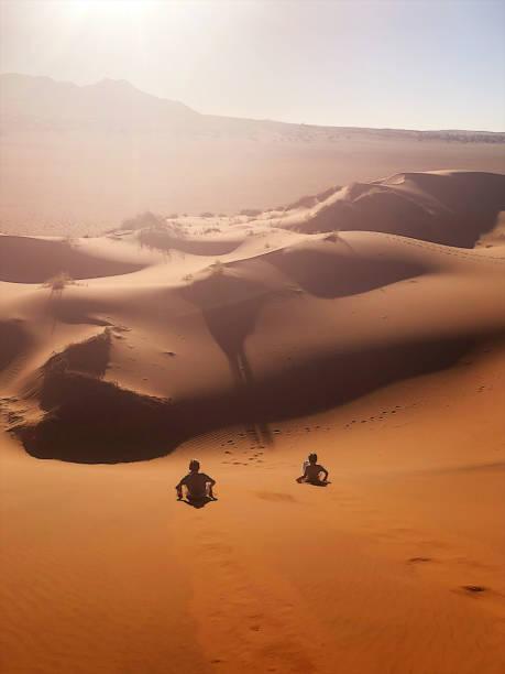 Red Sand dune sand boarding fun sliding down stock photo