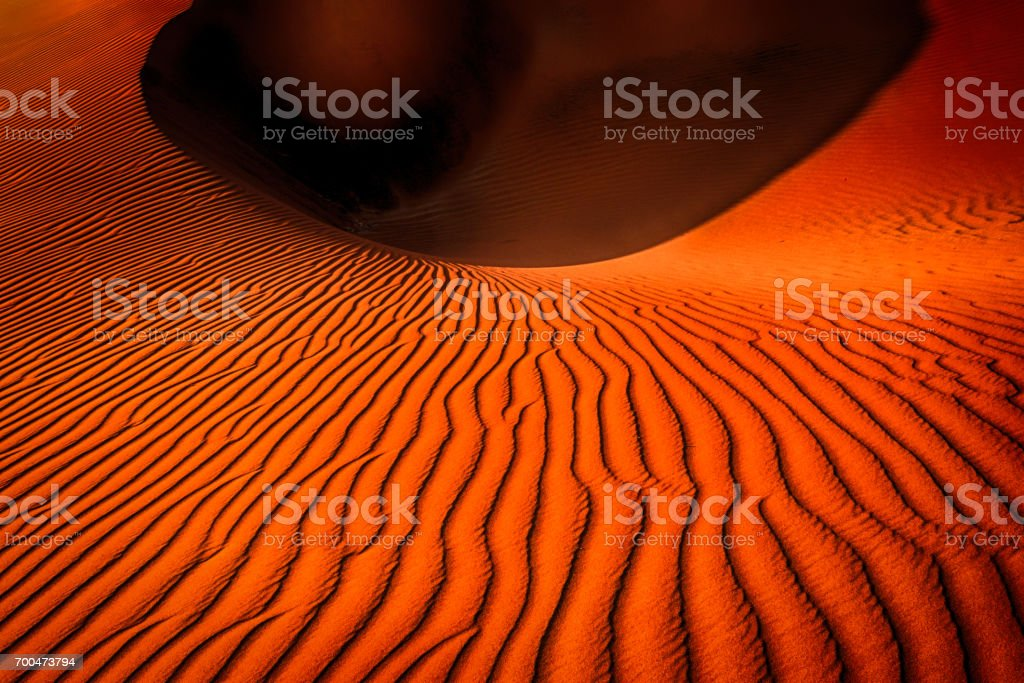 Red sand dune with a deep hole shaped like a crater, in Sossusvlei, Namibia. stock photo